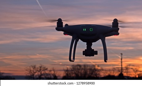 Geneva / Switzerland - Jan 05 2019: A drone hovers in flight in front of a sunset background. The drone is stationary hovering above the ground as the sunsets in the distance.