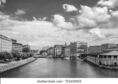 GENEVA, SWITZERLAND - JULY 10, 2017: Rhone River with left the Quai Turrettini and right the Quai des Moulins and on the bridge Rue des Moulins under on a sunny day in summer. Black and white image.