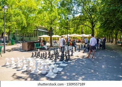 Geneva, Switzerland - July 19, 2019: People playing an outdoor chess game with giant chess pieces in the Parc des Bastions. Big chess boards are located at the entrance to the park in the city center.