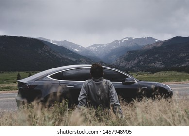 Geneva / Switzerland July 3rd 2019 : Photograph of a Tesla model 3 with a man in front of it with the Swiss mountains in the background.