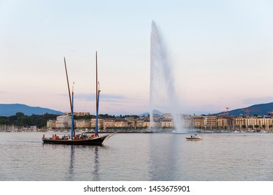 GENEVA, SWITZERLAND - JUNE 29, 2018: Wooden tour boat with tall masts near fountain Jet d'eau in lake Geneva, Switzerland on June 29, 2019