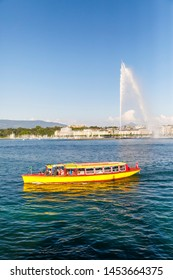 GENEVA, SWITZERLAND - JUNE 30, 2018: Small yellow cruise boat and 140m high fountain called Jet d'Eau in city centre of Geneva, Switzerland on June 30, 2018
