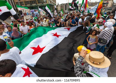 GENEVA, SWITZERLAND - JUNE 30: Unidentified protesters holding the syrian flag during a protest against President of Syria Bashar al Asaad in the city of Geneva, June 30, 2012 in Geneva, Switzerland.