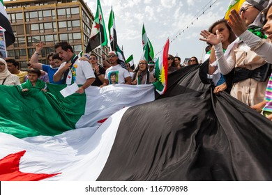GENEVA, SWITZERLAND - JUNE 30: Unidentified protesters walking with the syrian flag during a protest against President of Syria in the center of Geneva, June 30, 2012 in Geneva, Switzerland.