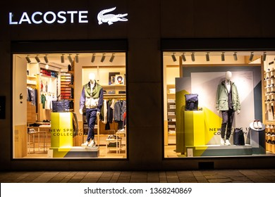 Geneva, Switzerland, March 09, 2019, Lacoste fashion store, window shop with modern clothes, blouses, pants, skirts, shoes, coats, jackets, jeans, shirts from Lacoste fashion house