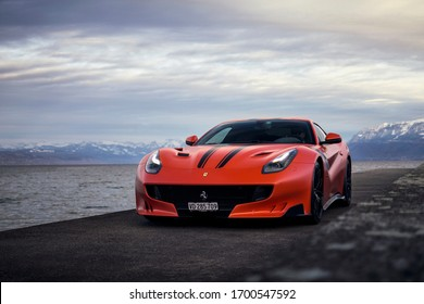 Geneva, Switzerland - March 2020: Ferrari F12tdf supercar in unique Rosso Dino Opaco colour parked on a fishing pier in rural Switzerland.