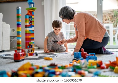 GENEVA, SWITZERLAND - MARCH 23, 2020: Little toddler boy playing with grandmother with Lego blocks at home at quarantine  period during coronavirus pandemic. Family leisure activity and communication