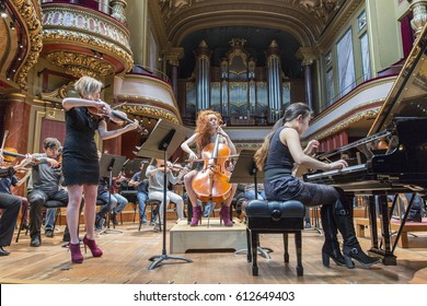 GENEVA, SWITZERLAND – MARCH 25, 2017: Cellist Camille Berthollet, violinist Julie Berthollet and pianist  Melodie Zhao playing during rehearsals for the UN Orchestra concert for the IOM.