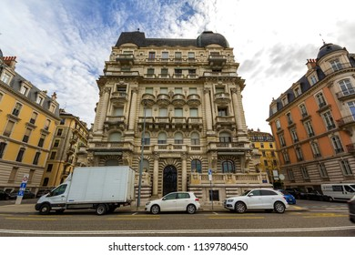 Geneva, Switzerland - March 9, 2018: New modern cars parked on street of historical center of Geneva city with view of old architechture buildings. Travelling in Europe and transportation concept.