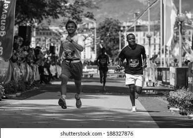 GENEVA, SWITZERLAND - MAY 6 : Two unidentified participants sprint side by side on the final stretch of the Geneva marathon 2012 .