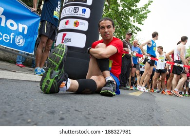 GENEVA, SWITZERLAND - MAY 6 : An unidentified participant of the Geneva marathon 2012 stretches before the beginning of the great final marathon race of the day.