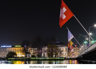 Geneva, Switzerland - November 24, 2016: Night cityscape with Swiss flag and illuminated facades on a riverside in central area of Geneva city