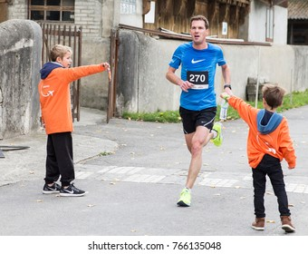 GENEVA, SWITZERLAND – OCTOBER 29, 2017: Volunteers offer refreshments to unidentified athlete participating in the inaugural edition of the Geneva 20km race.