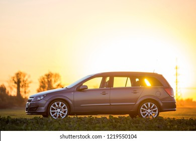 Geneva, Switzerland - October 9, 2018: Side view of gray silver empty car parked in countryside on blurred rural landscape and bright orange clear sky at sunset copy space background.