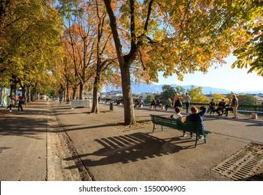 Geneva, Switzerland - Promenade de la Treille. People enjoying sunny autumn afternoon on the longest bench in the world, under yellow, orange and green leaves on the trees. Oct 14.2019.
