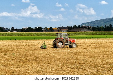Geneva, Switzerland - September 1, 2016: Tractor with plough doing some agricultural seasonal work at the field.