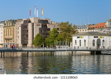 Geneva, Switzerland - September 24, 2016: people on a bridge over the Rhone river, building of the Cantonal Bank of Geneva in the background. Geneva is the capital of the Swiss canton of Geneva.