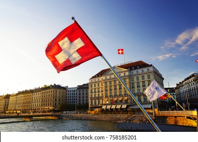 GENEVA, SWITZTERLAND - OCTOBER 27, 2017: Flag of the Geneva Canton and flag of Switerland in the city center of Geneva on the Mont Blanc Bridge (Pont du Mont Blanc) on the Leman lake