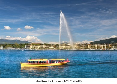 The Geneva Water Fountain, Jet d'Eau. One of the in Geneva famous yellow boats. Lake Geneva, Switzerland.