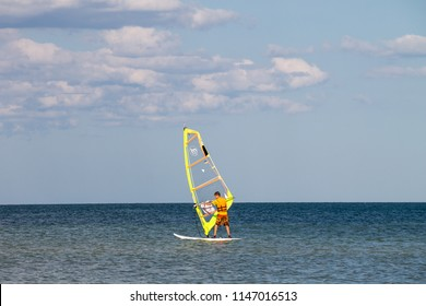 Genichesk, Ukraine - August 24, 2017: Windsurfing. Surfer exercising in calm Azov sea. Recreational water sports during idyllic summer vacation