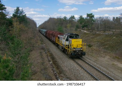 GENK, Belgium - April 16, 2021: LINEAS HLR 77-78 Grey-Yellow Diesel (Shunting) Locomotive with Sliding Wall Wagons Freight Train on Single Track Diesel Railway Line in Wooded and Natural Environment