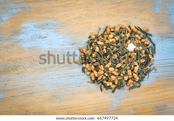 genmaicha green tea with roasted rice, a pile against grunge wood with a copy space