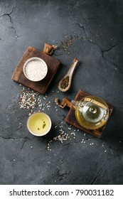 Genmaicha with roasted brown rice served in the glass tea pot and ceramic bowl and decorated with white rice in a bowl and fan. Over a stone board. Top View Copy Space