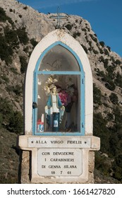 GENNA SILANA, SARDINIA, ITALY - OCTOBER 9th 2019 : White tabernacle topped by a cross with Virgin Mary statue in a white dress and a blue coat . It's a devotion to the policemen.