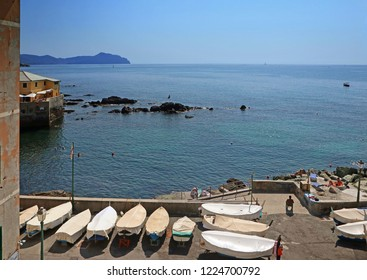 Genoa, Boccadasse - View of blue Tigullio gulf from the rocky shore of Boccadasse, picturesque quarter of Genoa with people sun bathing and fishing boats ashore