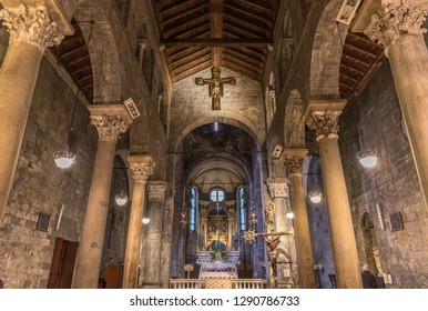 Genoa, Genova, Italy - January 2019: Interior of romanesque church Chiesa di San Donato: stone walls, wooden roofing (trusses), columns with decorated capitals, and wooden crucified Jesus (crucifix)