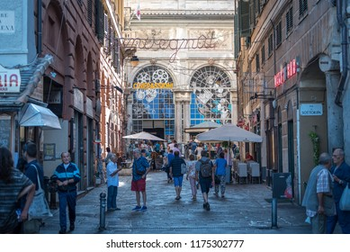 Genoa, Genova, Italy - September 8 2018: Tourists and locals walking around piazza Banchi and Loggia della Mercanzia in the old town, with traditional bar dehors