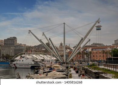 Genoa / Italy -  04 23 2019: View of the Old Port with the famous panoramic lift Bigo (1992) by the Genoese architect Renzo Piano, moored boats and the Palace of St. George (1260) in the background