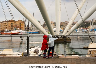 Genoa / Italy - April 23 2019: Two children from behind in rain suits in front of the famous Bigo (1992), a structure by the Genoese architect Renzo Piano inspired by the crane used in the naval field