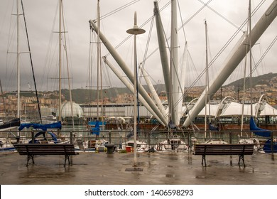Genoa / Italy - April 23 2019: Scenic view of the Old Port with the architectural structures Bigo (1992) and Biosphere (2001) by the Genoese architect Renzo Piano in a rainy day with overcast sky