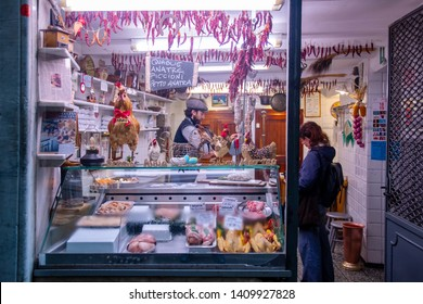 Genoa / Italy - April 23 2019: A butchery in Via dei Macelli (Slaughter Street), headquarter since the ancient times of abattoirs and butchers, with a butcher serving a client behind the shop window
