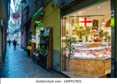 Genoa / Italy - April 23 2019: Street view with the illuminated shop window of a butchery in Via dei Macelli (Slaughter Street), headquarter since the ancient times of abattoirs and butchers