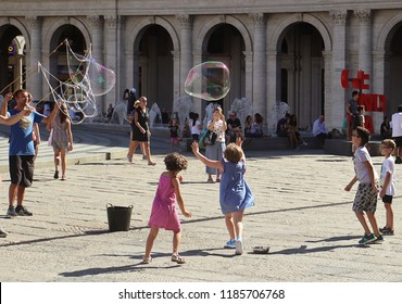 GENOA, ITALY - AUGUST 27, 2018 - Piazza de Ferrari in Genoa, boys and girls play with soap bubbles, pure happiness in a beautiful summer day