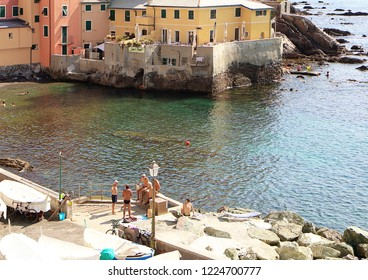 GENOA, ITALY - AUGUST 28, 2018 view of Boccadasse bay from the rocky shore, where people chat sunbathing leisurely