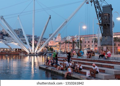 GENOA, ITALY - AUGUST 5, 2018: People resting at sea in the old port, Porto Antico in a summer evening. The panoramic lift Bigo offered a full view of the harbor and city, is visible on the back left