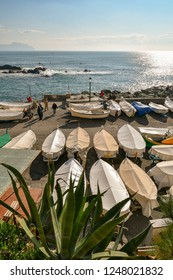 Genoa / Italy - February 12 2018: A glimpse of the old fishing village of Boccadasse, a neighborhood of Genoa, with people sunbathing and fishing boats on the quayside, Liguria