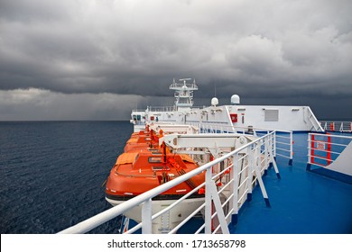 GENOA, ITALY - JULY 26, 2014: Lifeboats of a ferry boat in navigation, with a sky full of stormy clouds.