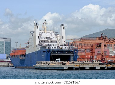 GENOA, ITALY - JUNE 10, 2015: The vessel CHODZIEZ a ro ro cargo ship. Boarding in the commercial port of Genoa of material and military vehicles for export.