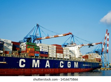 GENOA, ITALY - JUNE 4, 2019: the container ship CMA CGM LAMARTINE moored at the Sech terminal. Port cranes at work and the lighthouse symbol of the city in the background.