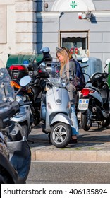 GENOA, ITALY - MARCH 19, 2015: Young beautiful girls traveling by a motorbike in genoa