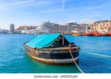 GENOA, ITALY - MARCH 9, 2019: Boat in the fair harbor on background cruise ship in Italian harbor Genoa