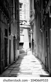 GENOA, ITALY - MAY 11, 2013  - Paved narrow street in old town Genoa, Italy, black and white, strong light contrast