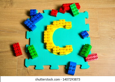 Genoa, Italy- May 25 2019 - Letter C composed of lego bricks on a play mat for children