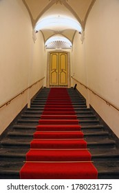 Genoa, Italy - October 10, 2017. Black stone staircase, with red carpet in the center, leading to a closed decoreted door in an ancient building. Rolli palace, Genoa.