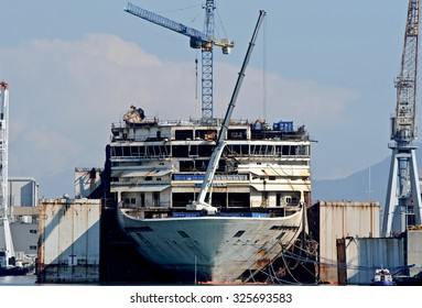 GENOA, ITALY - OCTOBER 7, 2015: The wreck of the Costa Concordia loses the bridges during the demolition. Workers and cranes working on the hull.