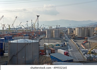 GENOA, ITALY - OCTOBER 9, 2016: Industrial complex by the Genoa harbour bay with cranes, trucks, containers.